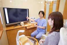 大型モニターを使った歯のシミュレーション画像を使った治療説明