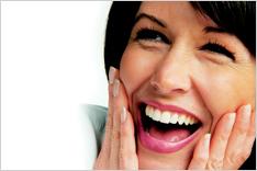笑顔で頬を押さえている女性