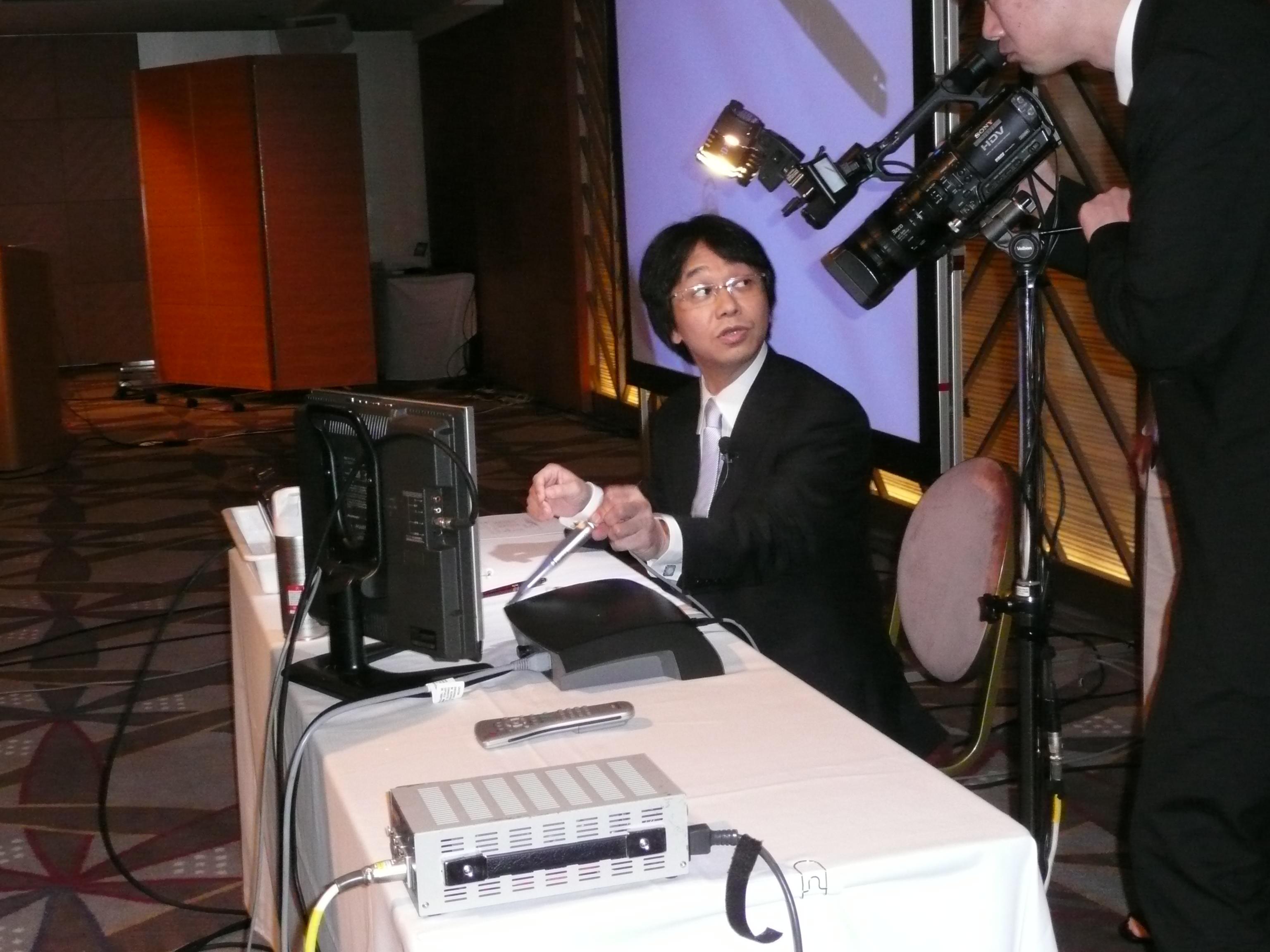 講演で使うパソコンの前に座っている加藤院長